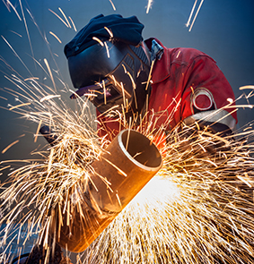 Welder working in the red uniform and a mask, he welds pipe bright sparks fly
